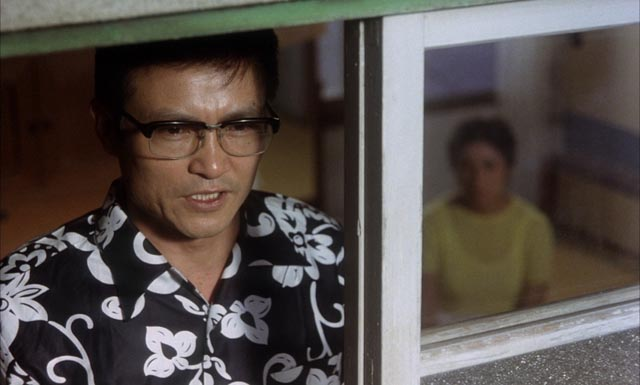 Ogata Ken as Enokizu Iwao , the nihilistic killer in Imamura Shohei's Vengeance Is Mine (1979)