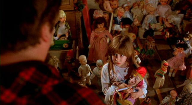 Carrie Lorraine as Judy, holding on to her Punch doll, in Stuart Gordon's creepy fairytale Dolls (1987)