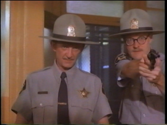 That's me, providing back-up for Police Chief Benny (Wayne Robson) in Paul Shapiro's Heads (1994): no, I didn't receive any training on how to hold a gun properly (frame grab from the long out-of-print VHS)