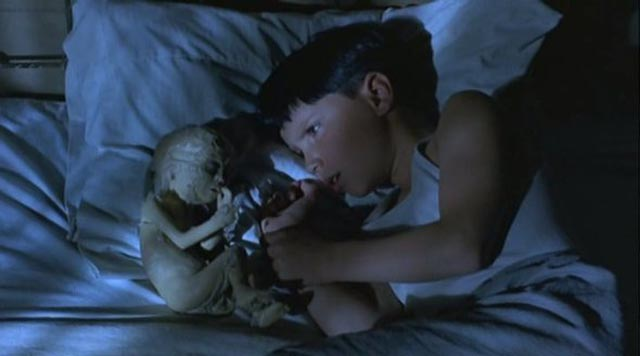 """Seth confers with his """"angel"""", a mummified baby discovered in the barn in Philip Ridley's The Reflecting Skin (1990)"""