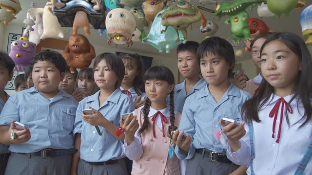The kids using handheld devices to control their critters in Takashi Murakami's Jellyfish Eyes (2013)