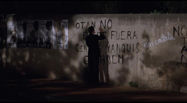 Fred (Chris Eigeman) attempts ineffectually to erase anti-American graffiti with a marker in Whit Stillman's Barcelona (1994)