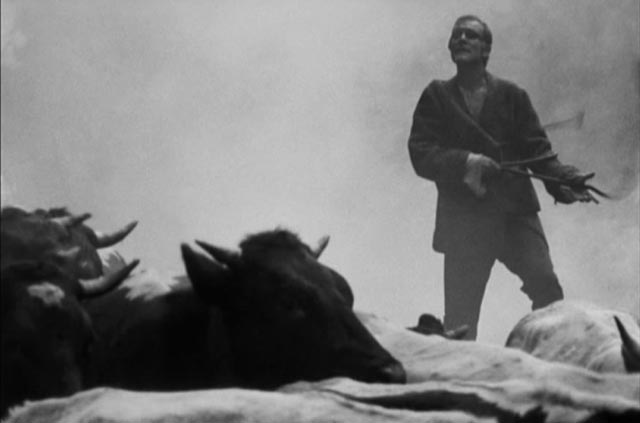Dragon (Radovan Lukavský) leads the village herd out of the burning forest in Eduard Grecner's Dragon's Return (1968)
