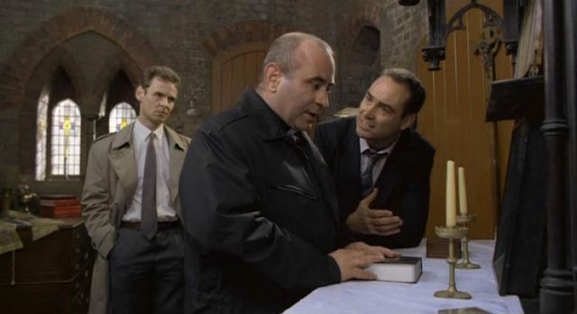 Father Michael Da Costa (Bob Hoskins) refuses to cooperate with the police in Mike Hodges' A Prayer for the Dying (1987)