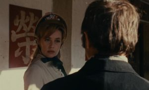 Virginie (Jeanne Moreau) approached on the street by Levinsky (Roger Coggio) in Orson Welles' The Immortal Story (1968)
