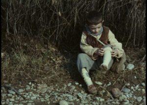 Minek (Omar Brignoli) tries to fix his broken shoe in Ermanno Olmi's The Tree of Wooden Clogs (1978)