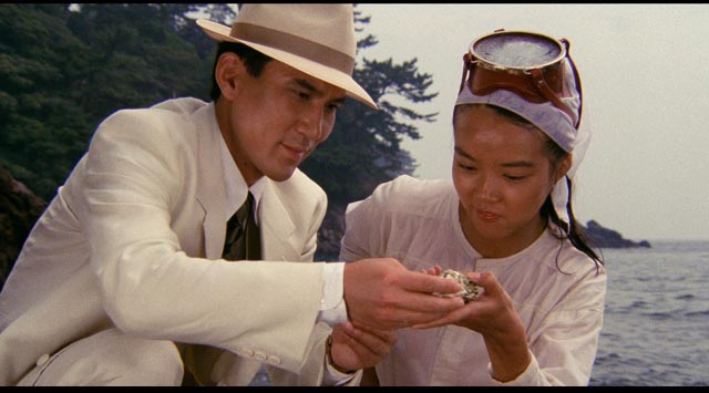 The man in white enjoys an oyster with a virginal oyster fisher in Juzo Itami's Tampopo (1985)