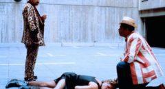 Jensen (Rainer Werner Fassbinder) and his sidekick Anton (Gunther Kaufmann) inspect a dead assassin in Wolf Gremm's Kamikaze '89 (1982)