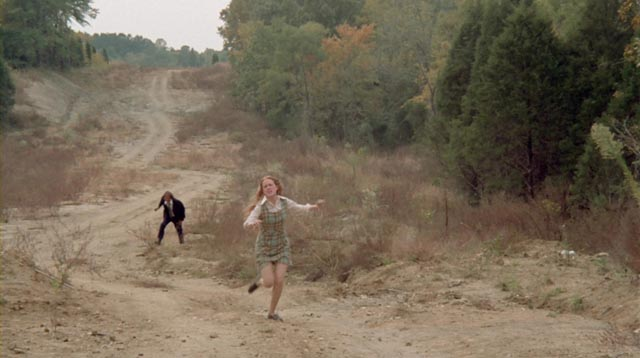 Sandra (Leslie Ann Rivers) runs from Eddie (Jack Canon), though by now he has become her protector in Frederick R. Friedel's Kidnapped Coed (1975)