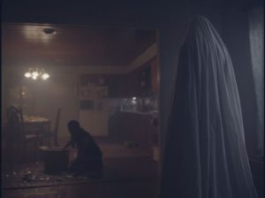 The ghost watches the house's new occupant clean up the mess he's made in David Lowery's A Ghost Story (2017)