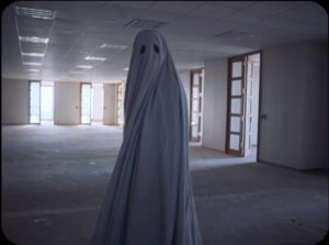 The ghost of C prowls through the building erected on the site of his demolished home in David Lowery's A Ghost Story (2017)