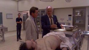 Cop Robert Loggia shows psychiatrist Martin Sheen what's been found in a dead man's belly in John Schlesinger's The Believers (1987)