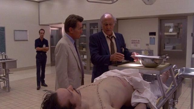 Cop Robert Loggia shows psychiatrist Martin Sheen what's been found in a dead man's belly in John Schlesinger's The Believers (1987)