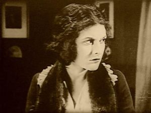 Nora (Evelyn Brent) realizes almost too late that she's in dire danger in Harry B. Parkinson's Trapped By the Mormons (1922)