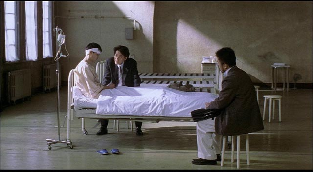 Police interrogate a man who inexplicably murdered his wife after meeting Mamiya in Kiyoshi Kurosawa's Cure (1997)