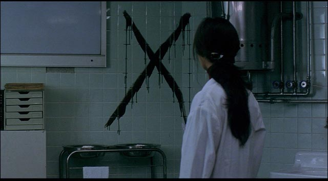 A doctor discovers the sign of the killer after examining Mamiya in Kiyoshi Kurosawa's Cure (1997)