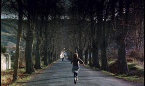 Estrella (Sonsoles Aranguren) runs to meet her father Agustin (Omero Antonutti) on his motorcycle in Victor Erice's El Sur (1983)