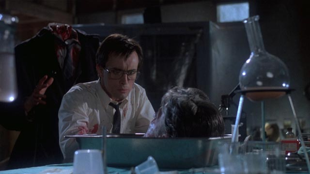 Herbert West (Jeffrey Combs) chats with the revived head of his academic nemesis in Stuart Gordon's Re-Animator (1985)
