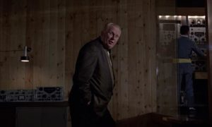 Gert Frobe as Goldfinger, casual about James Bond's imminent death