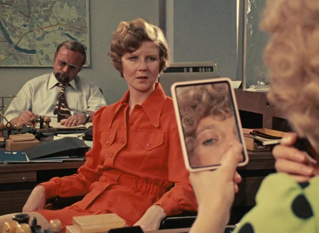 Marion (Hanna Schygulla)'s co-worker Irmgard (Irm Hermann) also disapproves of Jochen (Gottfried John) in Rainer Werner Fassbinder's Eight Hours Don't Make a Day (1972-73)