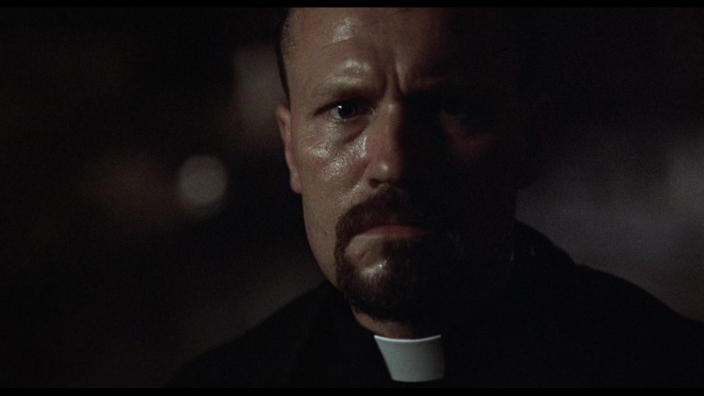 Michael Rooker as an angry demon-fighting priest in Jamie Dixon's Shadowbuilder (1998)