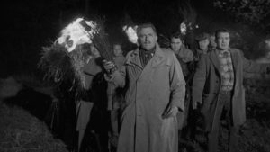 The villagers view the children with horror and form a traditional torch-wielding mob in Wolf Rilla's Village of the Damned (1960)
