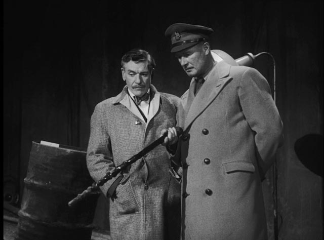 Quatermass (Andre Morrell) and Colonel Breen (Anthony Bushell) examine the strange find at a construction site in Nigel Kneale's Quatermass and the Pit (1959)