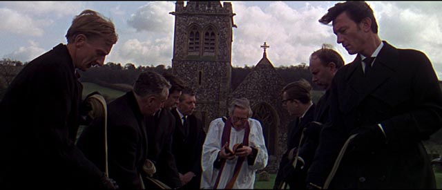 Alexander Eberlin (Laurence Harvey) attends the funeral of a fellow spy in Anthony Mann's A Dandy in Aspic (1968)