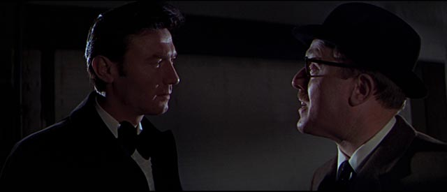 Eberlin (Laurence Harvey) confronts irritating agency bureaucrat Copperfield (Norman Bird) in Anthony Mann's A Dandy in Aspic (1968)