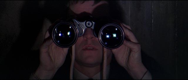 British agent Gatiss (Tom Courteney) spies on fellow spy Eberlin (Laurence Harvey) in Anthony Mann's A Dandy in Aspic (1968)