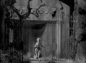Kitty (Veronica Hurst) runs from the castle in fear in William Cameron Menzies' The Maze (1953)