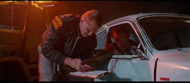 A tow truck driver gets a dying accident victim to sign a waiver in Brian Trenchard-Smith's Dead-End Drive-In (1986)