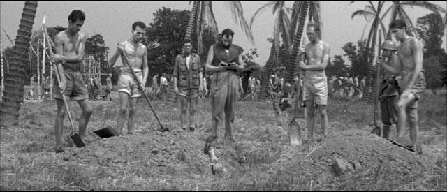 Chaplain Paul Anjou (Michael Goodliffe) delivers messages between camps in Latin during funerals in Val Guest's The Camp on Blood Island (1958)