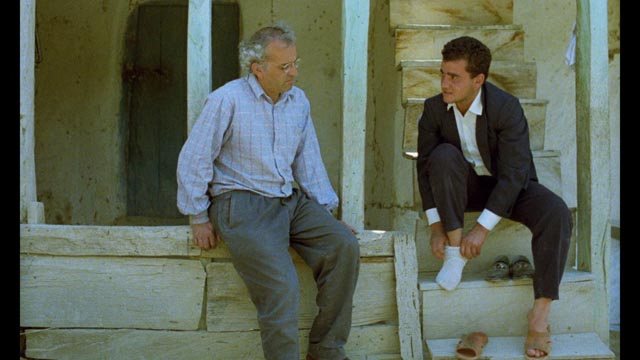 Pausing for a while, the Director (Farhad Kheradmand) meets newly married Hossein (Hossein Rezai) in Abbas Kiarostami's And Life Goes On (1992)