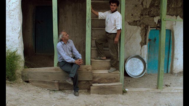 Hossein (Hossein Rezai) and the Director-character (Farhad Kheradmand) listen to the Director's instructions between takes in Abbas Kiarostami's Through the Olive Trees (1994)