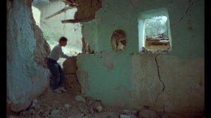 The Director's son Pouya (Pouya Payvar) explores the ruins of Poshteh in Abbas Kiarostami's And Life Goes On (1992)