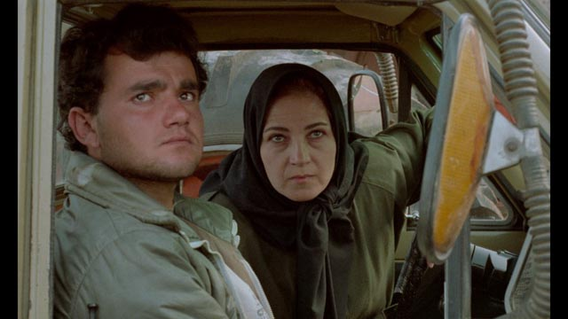 Hossein (Hossein Rezai) is picked up and coached by the Director's assistant Mrs Shiva (Zahrifeh Shiva) in Abbas Kiarostami's Through the Olive Trees (1994)