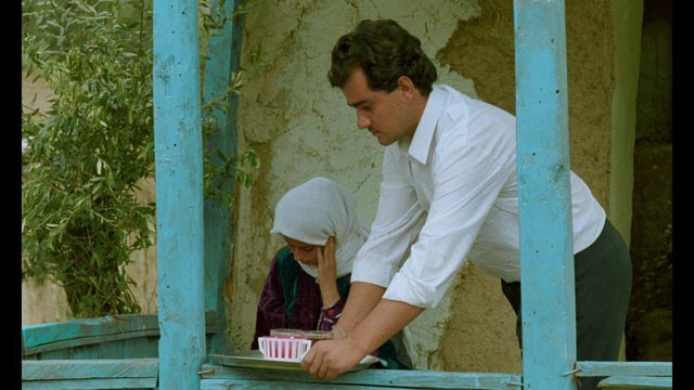 Between takes, Hossein (Hossein Rezai) offers Tahereh (Tahereh Ladanian) tea in Abbas Kiarostami's Through the Olive Trees (1994)