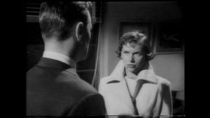 Caroline Cartier (Muriel Pavlov) warns Brian Johnson (Patric Doonan) that Heathley (James Donald)'s obsession is dangerous in Anthony Asquith's The Net (1953)