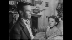 Michael Heathley (James Donald), immersed in his work, neglects his marriage to Lydia (Phyllis Calvert) in Anthony Asquith's The Net (1953)