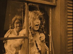 Elsie Stoneman (Lillian Gish) watches horrified as Free Blacks rampage in the streets in D.W. Griffith's Birth of a Nation (1915)