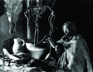 Brewing potions in a witch's kitchen in Benjamin Christensen's Haxan (1922)