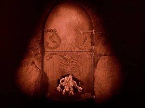 An imp breaks through a door in stop motion in Benjamin Christensen's Haxan (1922)