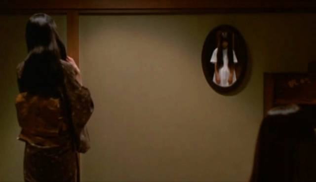 Shizuko (Masako) brushes her hair with Sadako (Rie Ino'o) reflected in the mirror in Hideo Nakata's Ring 2 (1999)