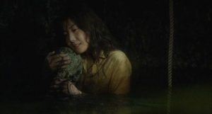 Reiko (Nanako Matsushima) comforts the rotting remains of Sadako at the bottom of the well in Hideo Nakata's Ringu (1998)