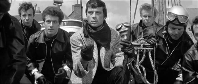 King (Oliver Reed) and his leather gang menace an American tourist in Joseph Losey's The Damned (1962)