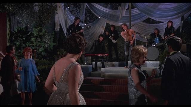 Tara (Holly Near) is drawn to singer Bogart Peter Stuyvesant (Jordan Christopher) at her coming out party in Robert Thom's Cult of the Damned (1969)