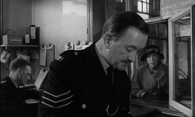 A patient policeman (Jack Austin) reassures Mrs Ross (Edith Evans) that her fears are taken seriously in Bryan Forbes' The Whisperers (1967)