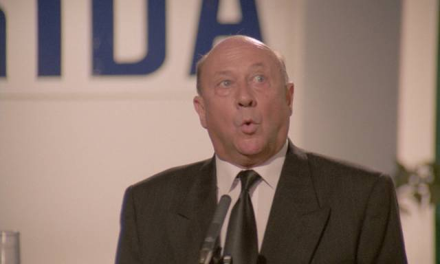 Reverend Mortom (Donald Pleasence) loses control of his mouth at an awkward time in Sergio Martino's American Rickshaw (1989)
