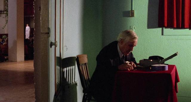 Walter Travis (Jason Robards) counts cash while daughter Martha (Rosanna Arquette) offers her visions to the congregation in Mike Hodges' Black Rainbow (1989)